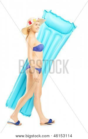 Full length portriat of a female in bikini walking with air mattress, isolated on white background