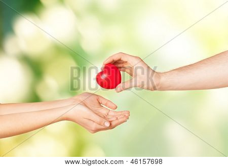 close up of man hand giving heart to woman