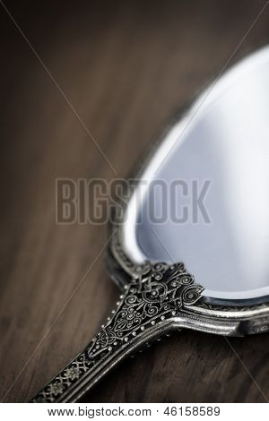 Antique gilded hand mirror, over dark timber.  Soft focus.