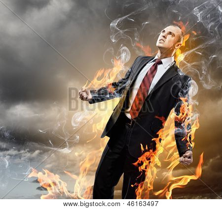Image of young businessman in anger burning in fire
