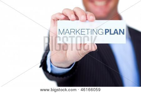 Businessman holding a label with marketing plan written on it on white background
