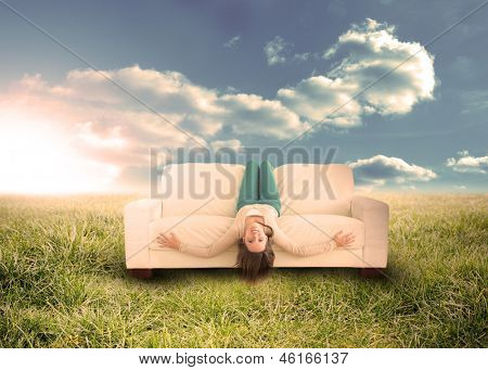 Silly woman sitting upside down on couch in sunny field in countryside