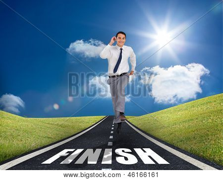 Smiling businessman running on a road with finish written on it