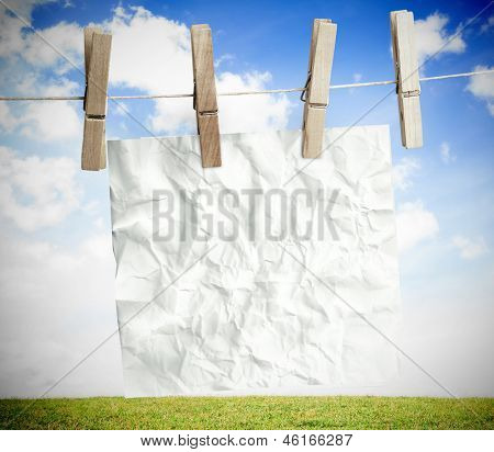 White crumpled paper hung on a laundry line with bright blue sky on the background