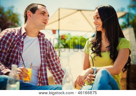 young happy couple drink  refreshments in cafe outdoor summer day