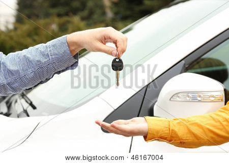 Woman and man hands with car key, close up