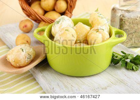 Concursos jovens batatas com creme de leite e ervas no pan na placa de madeira em close-up tabela