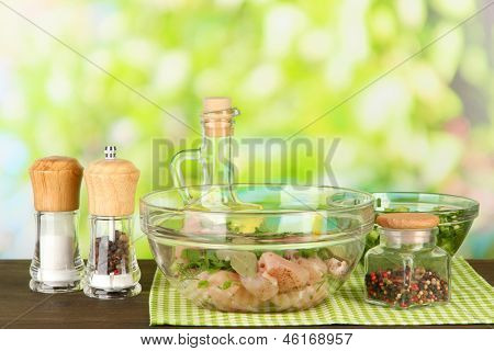Chicken meat in glass bowl,herbs and spices on table on nature background
