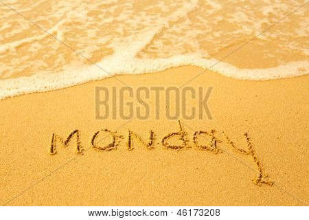 Monday - written in sand on beach texture, soft wave of the sea.