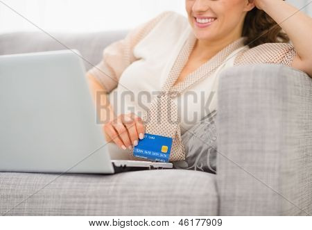 Closeup On Credit Card In Hand Of Smiling Woman With Laptop
