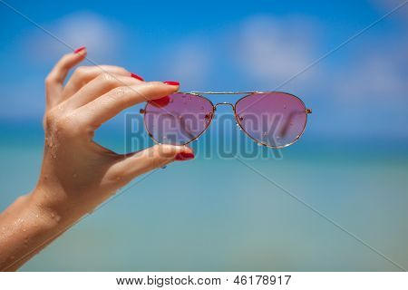 Womans Hand Holding Sunglasses On Tropical Beach