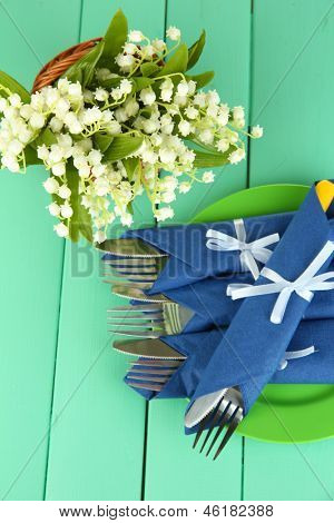 Fork and knife wrapped in blue paper napkin, on color wooden background
