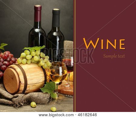 Still life of wine, grapes and cheese on wooden table on grey background