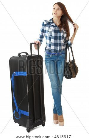 Slim Girl In Jeans And A Plaid Shirt, Standing Next To A Big, Black Travel Bag On Wheels.