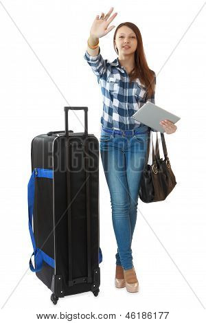 Young Traveler With A Huge, Black Travel Bag On Wheels, Waving His Hand, Drawing The Attention Of Gr