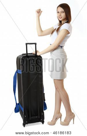 A Young, Slim Girl Teenager 16 Years Old, Stands Next To A Huge, Black Suitcase On Wheels.