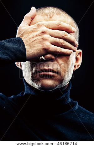 Close-up portrait of a man with closed eyes over black background.