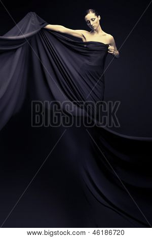 Art fashion photo of a beautiful woman in black dress. Over black background.