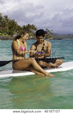 Couple, CellPhone On PaddleBoard