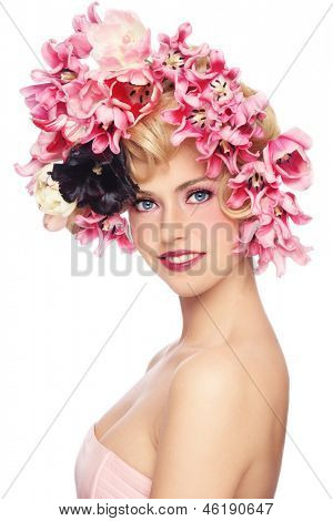 Portrait of young beautiful smiling girl with stylish make-up and colorful flowers on her hair, on white background