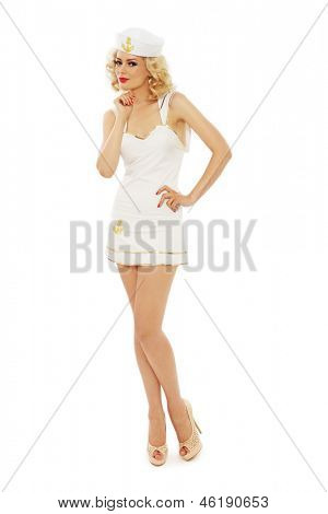 Young beautiful slim sexy girl with blond curly hair and stylish make-up dressed as sailor, over white background