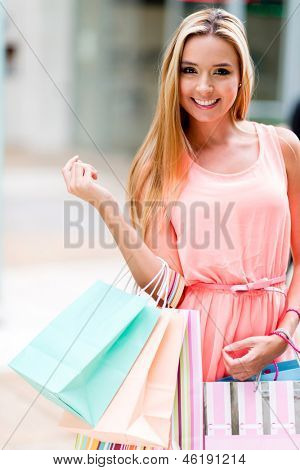 Happy female shopper holding shopping bags and smiling