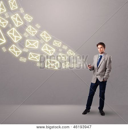 attractive young man standing and holding a phone with message icons