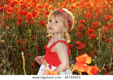 Funny Little Girl In Red Poppies Filed, Sunset. Outdoors Portrait. Cute Child Girl