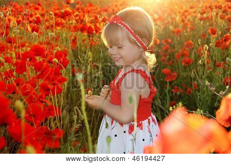 Happy Smiling Little Girl In Red Poppies Filed, Sunset. Outdoors Portrait. Cute Child Girl