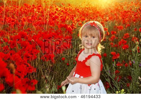 Smiling Little Girl In Red Poppies Filed, Sunset. Outdoors Portrait. Cute Child Girl