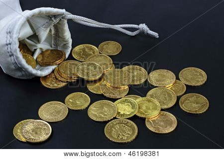 purse with gold coins on hte black background