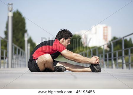 Athlete male at the city park warming and stretching