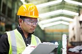 stock photo of clipboard  - Factory worker writing on clipboard was checking work - JPG