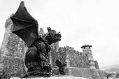 image of gargoyles  - A gargoyle stands guard with his twin outside of a medieval castle in black and white - JPG