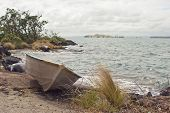 stock photo of scoria  - A dinghy rests on the shore of Rangitoto Island in the Hauraki Gulf of New Zealand - JPG