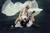 picture of white gown  - Bride playing rock guitar over artistic dark background - JPG