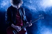 stock photo of guitarists  - Young Man Playing Electric Guitar in a Live Concert - JPG