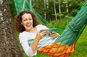 foto of birchwood  - Young smiling woman lies in hammock with tablet PC outdoors at birchwood - JPG