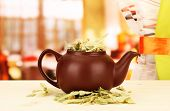 stock photo of tansy  - Dried herbs in teapot on wooden table - JPG
