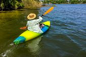 image of kayak  - Woman in a straw hat rowing away from shore in her kayak on a beautiful river or lake - JPG