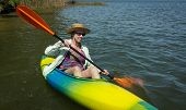 stock photo of kayak  - Mature woman paddling a small kayak on a sunny day - JPG