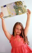 stock photo of nyse  - Little Child holding 100 Euro in the hands - JPG