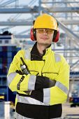 Portrait of a confident docker, wearing all required personal protective equipment, posing in front