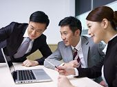 stock photo of debate  - a team of asian business people working together in office.