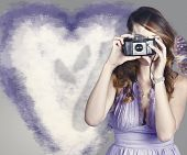 stock photo of soulmate  - Old fashioned woman holding retro camera pressing shutter button when trying to capture the movement of two love butterflies - JPG