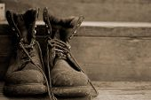 image of work boots  - Old ratty pair of work boots on the steps - JPG