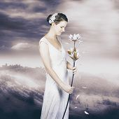 picture of idealistic  - Sentimental woman on mountain lookout wearing vintage wedding gown holding flower with falling petals - JPG