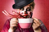 image of mutilated  - Creepy female zombie holding big soup cup containing severed and mutilated hand - JPG