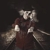 stock photo of gory  - Eerie photograph of a zombie walking down train tracks with arms stretched out in undead vintage style - JPG