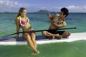 stock photo of two women taking cell phone  - couple taking pictures with cell phone on a paddle board in the ocean - JPG